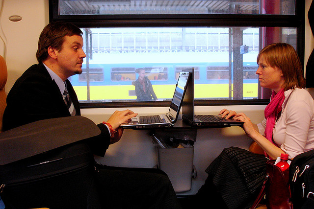 A man and woman using laptops on a train