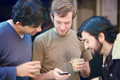 Three guys looking at a smartphone.