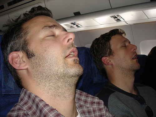 Two guys sleeping in a plane